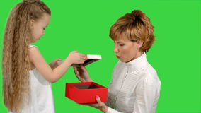 Pretty caucasian woman getting chrismas gift from her daughter on a green screen, chroma key stock video