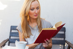 A pretty caucasian woman at home reading on the porch and drinki Royalty Free Stock Photo