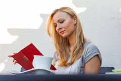 A pretty caucasian woman at home reading on the porch and drinki Stock Photos