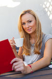 A pretty caucasian woman at home reading on the porch and drinki Stock Photography
