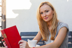 A pretty caucasian woman at home reading on the porch and drinki Royalty Free Stock Image
