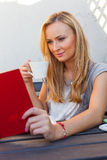 A pretty caucasian woman at home reading on the porch and drinki Royalty Free Stock Photos