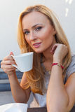 A pretty caucasian woman at home reading on the porch and drinki Royalty Free Stock Photography