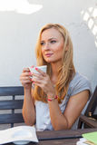 A pretty caucasian woman at home sitting on the porch and drinking coffee Royalty Free Stock Image