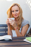 A pretty caucasian woman at home sitting on the porch and drinking coffee Stock Photography