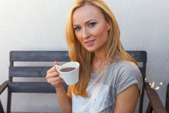 A pretty caucasian woman at home sitting on the porch and drinking coffee Stock Photo