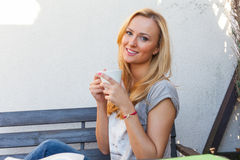 A pretty caucasian woman at home sitting on the porch and drinking coffee Stock Photos