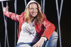 Pretty caucasian Woman In red Leather Jacket and Blue Jeans Posing in Hoodie Stock Photography