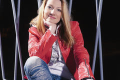 Pretty caucasian Woman In red Leather Jacket and Blue Jeans Posing Outdoors on Street at Night Stock Images