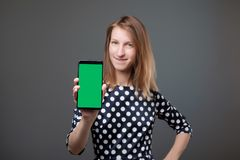 Pretty caucasian woman showing mobile smartphone with green screen in vertical position isolated on green background. royalty free stock photo