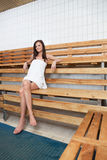 Pretty Caucasian woman sitting on a bench Royalty Free Stock Photography