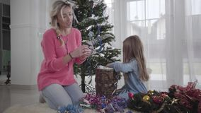 Pretty Caucasian woman talking to little girl and taking Christmas decoration. Happy mother helping daughter to choose. Decorations before Christmas stock video footage