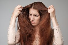 Pretty caucasian woman trying to comb hair. Royalty Free Stock Photography