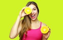 Pretty charming joyful attractive cheerful funny positive natural girl having two pieces of orange hide one eye isolated on yellow. Background with copy space stock images