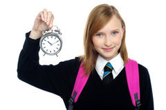 Pretty charming schoolgirl holding time piece Royalty Free Stock Image
