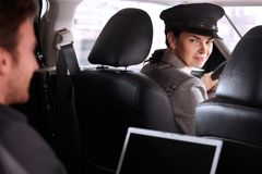 Pretty chauffeur in luxury car Stock Photos