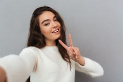 Pretty cheerful brunette woman showing peace gesture while takin Royalty Free Stock Image