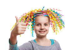 Pretty cheerful girl portrait. child with colorful swirls of paper in her hair smiling. Positive human emotions. Royalty Free Stock Images