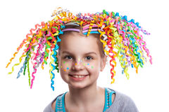 Pretty cheerful girl portrait. child with colorful swirls of paper in her hair smiling. Positive human emotions Royalty Free Stock Images