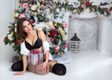 Pretty cheerful girl sitting with gift box near Christmas tree. Sexy young woman in black lingerie and shirt in Christmas interior Royalty Free Stock Image