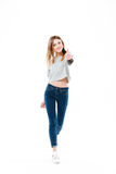 Pretty cheerful girl standing and showing thumbs up gesture Royalty Free Stock Photo