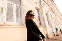 Pretty cheerful hipster young woman in dark stylish sunglasses in long fashionable coat with a handbag posing on the street. Near a vintage building. Joyful royalty free stock photos