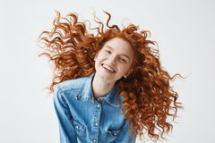 Pretty cheerful redhead girl with flying curly hair smiling laughing looking at camera over white background. Pretty happy cheerful redhead girl with Royalty Free Stock Photos