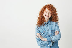 Pretty cheerful redhead girl with flying curly hair smiling laughing looking at camera over white background. Royalty Free Stock Photography