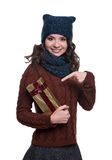 Pretty cheerful young woman wearing knitted sweater, scarf and hat, holding christmas gift. Isolated on white background. She Stock Photos