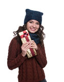 Pretty cheerful sexy young woman wearing knitted sweater, scarf and hat, holding christmas gift. Isolated on white background. Stock Photos