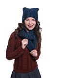Pretty cheerful young woman wearing knitted sweater, scarf and hat. Isolated on white background. She is smiling. Royalty Free Stock Images