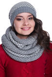 Pretty cheerful young woman wearing knitted sweater, scarf and hat. Isolated on white background. She is smiling. Stock Photography