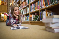 Pretty cheerful student lying on library floor reading book Stock Image