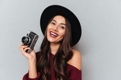Pretty cheerful woman in black hat holding retro photo camera Stock Photo