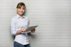 Pretty cheerful Woman holding a Tablet Pc, isolated over a gray Stock Image