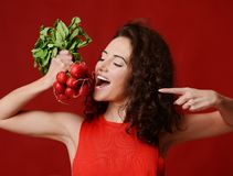 Pretty cheerful young sport woman hold fresh radish with green leaves and pointing finger. Dieting. Healthy eating concept on red background Stock Images