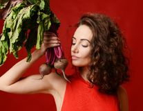 Pretty cheerful young sport woman posing with fresh beetroot green leaves. Stock Photos