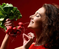 Pretty cheerful young sport woman posing with fresh radish green. Leaves. Dieting. Healthy eating concept on red background Royalty Free Stock Image