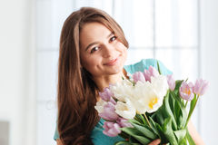 Pretty cheerful young woman with bouquet of flowers Stock Photos