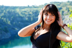 Pretty cheerful young woman listening to music in headphones outd. Oors. walking on a mountains at sunny summer day stock photos