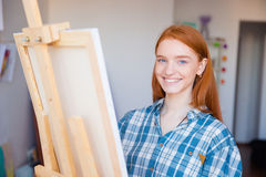 Pretty cheerful young woman painter painting in art studio Stock Images