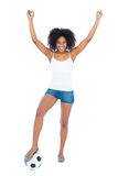 Pretty cheering girl in white top and denim hot pants with football Royalty Free Stock Image
