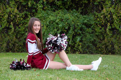 Pretty Cheerleader. Pretty young cheerleader wearing a maroon colored uniform and pompoms posing outdoors on lawn Stock Photos