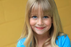 Pretty Child. Pretty blond child smiling in blue and yellow Stock Photos