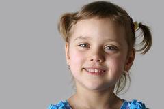 Pretty child. Face of pretty smiling girl, close-up, gray background Stock Photo