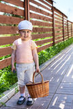 Pretty child with basket walking on house courtyard Stock Photos