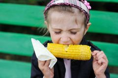 Pretty child girl eats a boiled corn Royalty Free Stock Photos