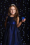 Pretty child girl is holding blue christmas ball Stock Photo