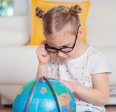 Pretty child girl at home dreaming of travel and tourism, explor Royalty Free Stock Images