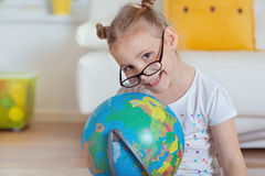 Pretty child girl at home dreaming of travel and tourism, explor Stock Photo